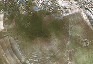 Foto aérea del entorno del Cabezo del Carmolí, en 2004. La forma de media luna del monte sugiere que el cráter se situaría en la zona deprimida y con mayor vegetación de la derecha [LIG Carmolí]
