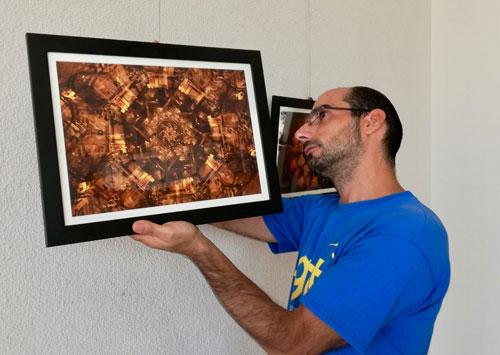 Antonio Martínez Tomás coloca una de sus fotografías de la serie 'La magia de la noche'